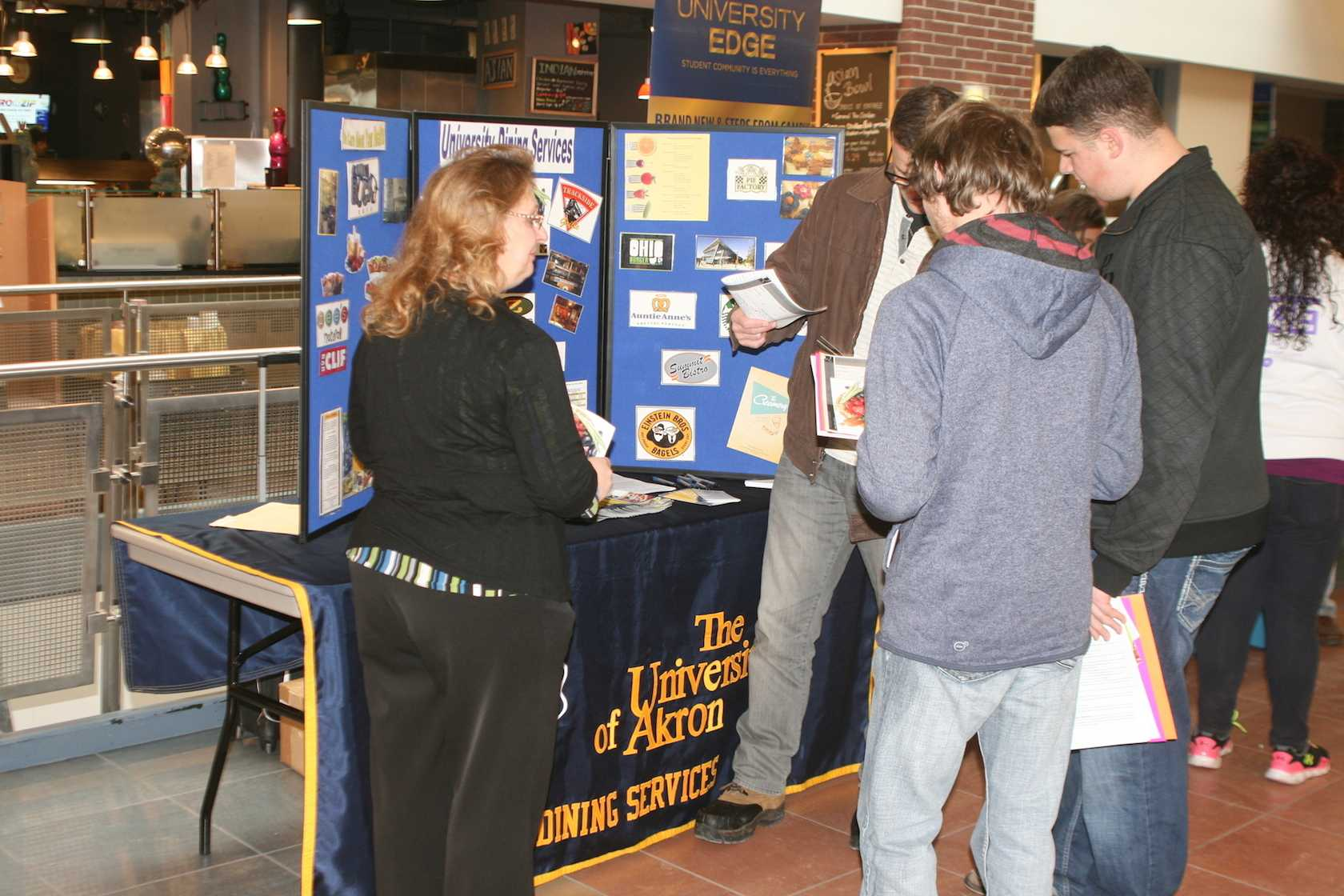Three students receive dining plan information in front of the UA Dining Services table.