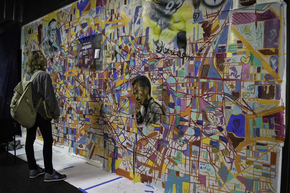 UA student Ben Holda, a sophomore, admires an artistic rendition of a map of Akron at Big Love Fest.