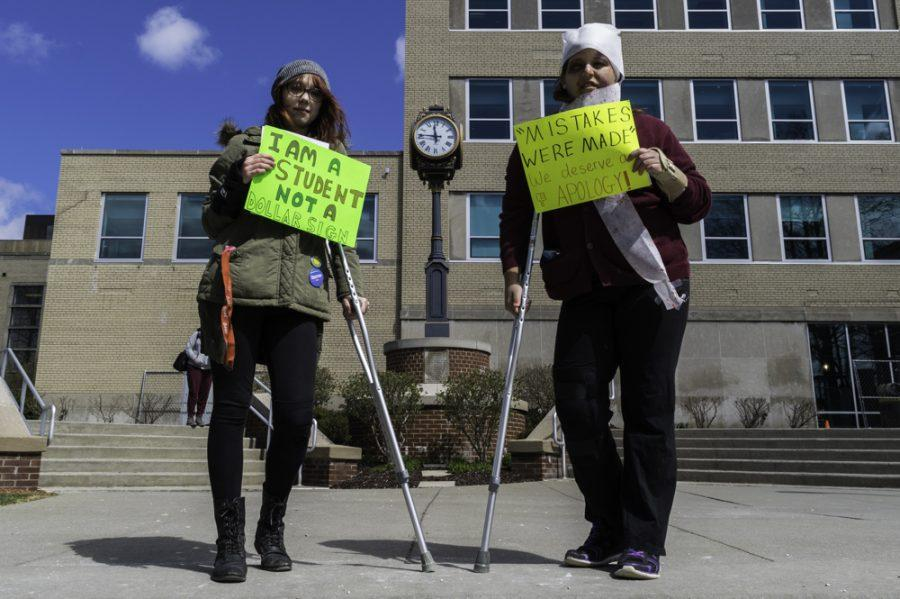 "Two ""wounded"" students, Angelica Corrado and Kasey Serrano, protesting against University leadership outside the Student Union on Tuesday, a day before the Board meeting."