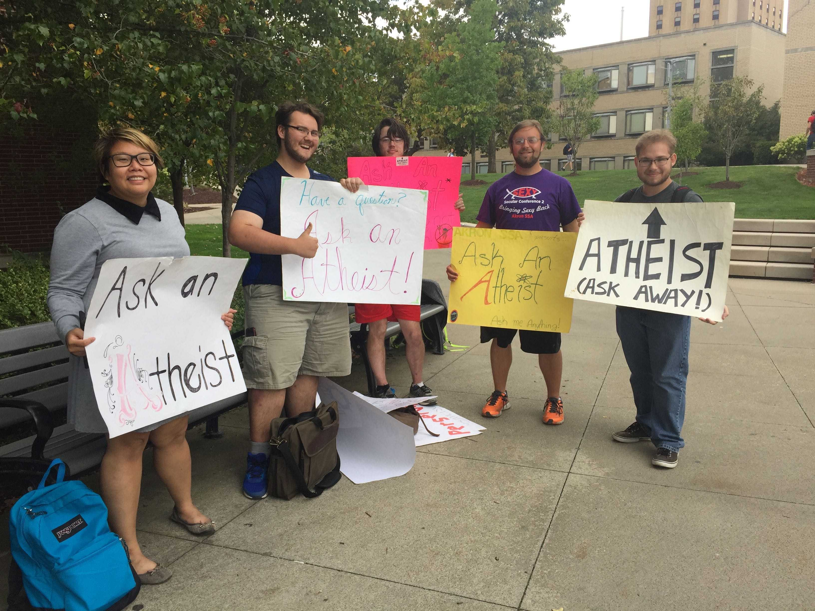 Members of the Secular Student Alliance Van Tran, Daniel Schuhmacher, Nicholas Hurt, Nicholas Kogovosek, and Ron Swanson hold up signs at their annual