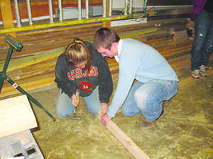 University of Akron students Heather Smeltzer and Daniel Darkow are working on constructing a side of a shed. The shed will be used to store tools on site at a habitat house that is being built.