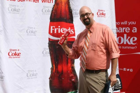 Joe McCartney poses with his two personalized Coca-Cola cans.