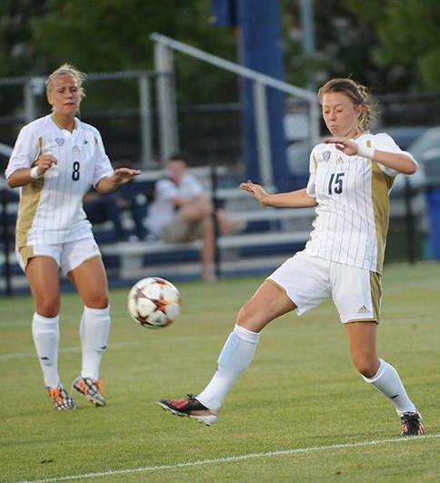 Brooke Carrel (15) running with the ball with Jenna Andersen (8) looking on.