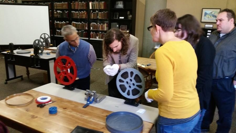 Visiting instructor Bleakley McDowell shows how to properly inspect 16-millimeter film.