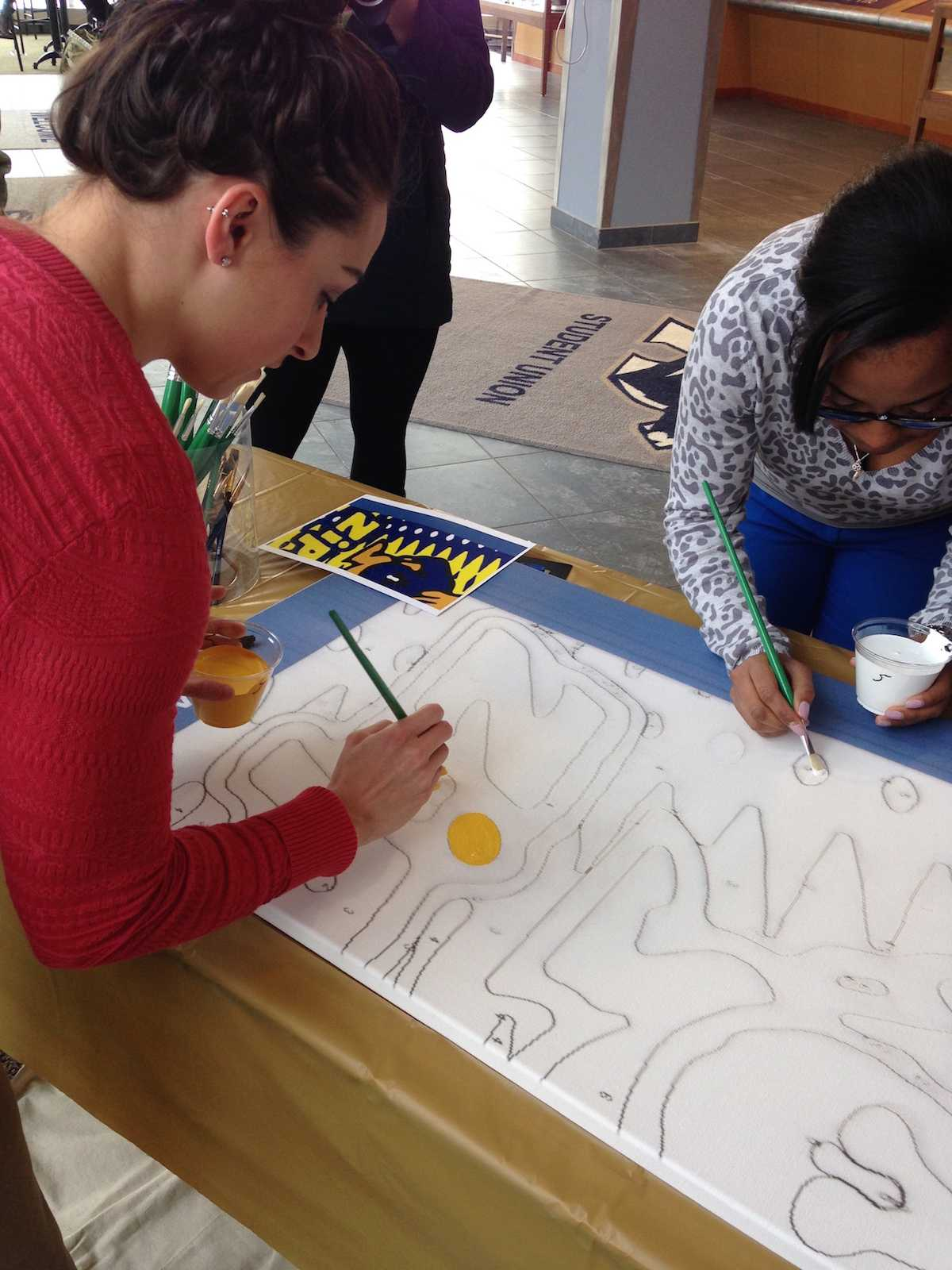 Katie Schneider (left) and Ursulla Jefferson (right) are first to paint on UA's mural.