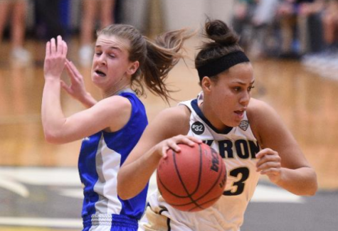DiAndra Gibson passing by a UB defender on her way to make a layup.