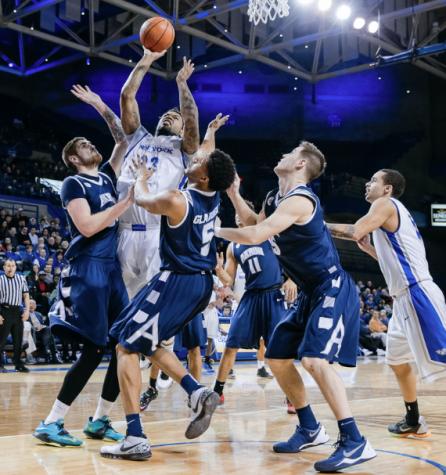 Akron basketball players playing defense against Buffalo.