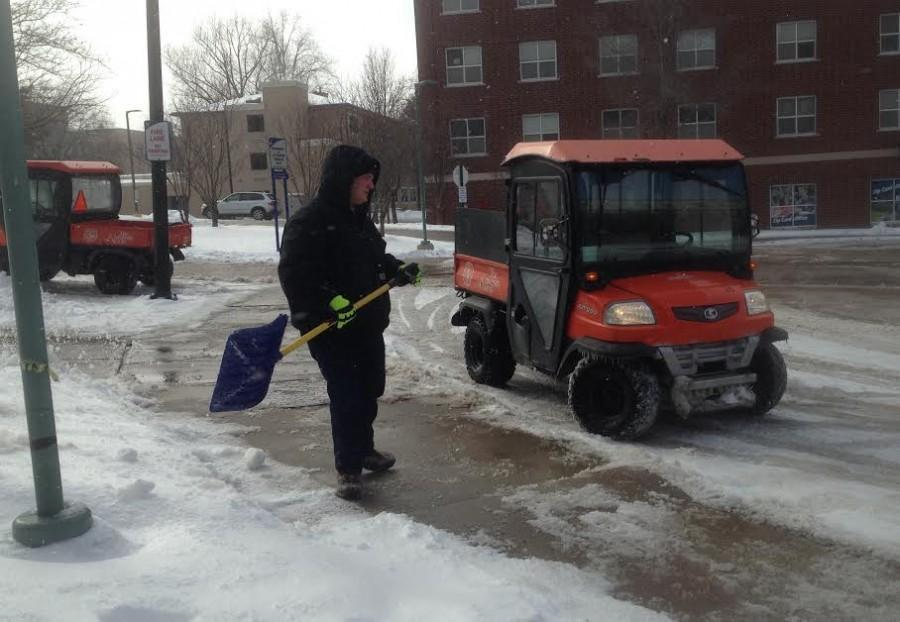 Jackson Liebler, a fourth-year political science major, shovels snow behind Bierce Library as part of the UA grounds crew.