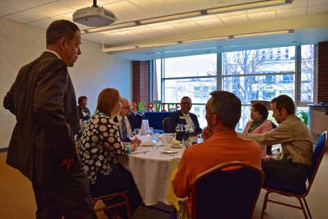 The faculty who attended the luncheon socialize on the topic of the day before the food is served.