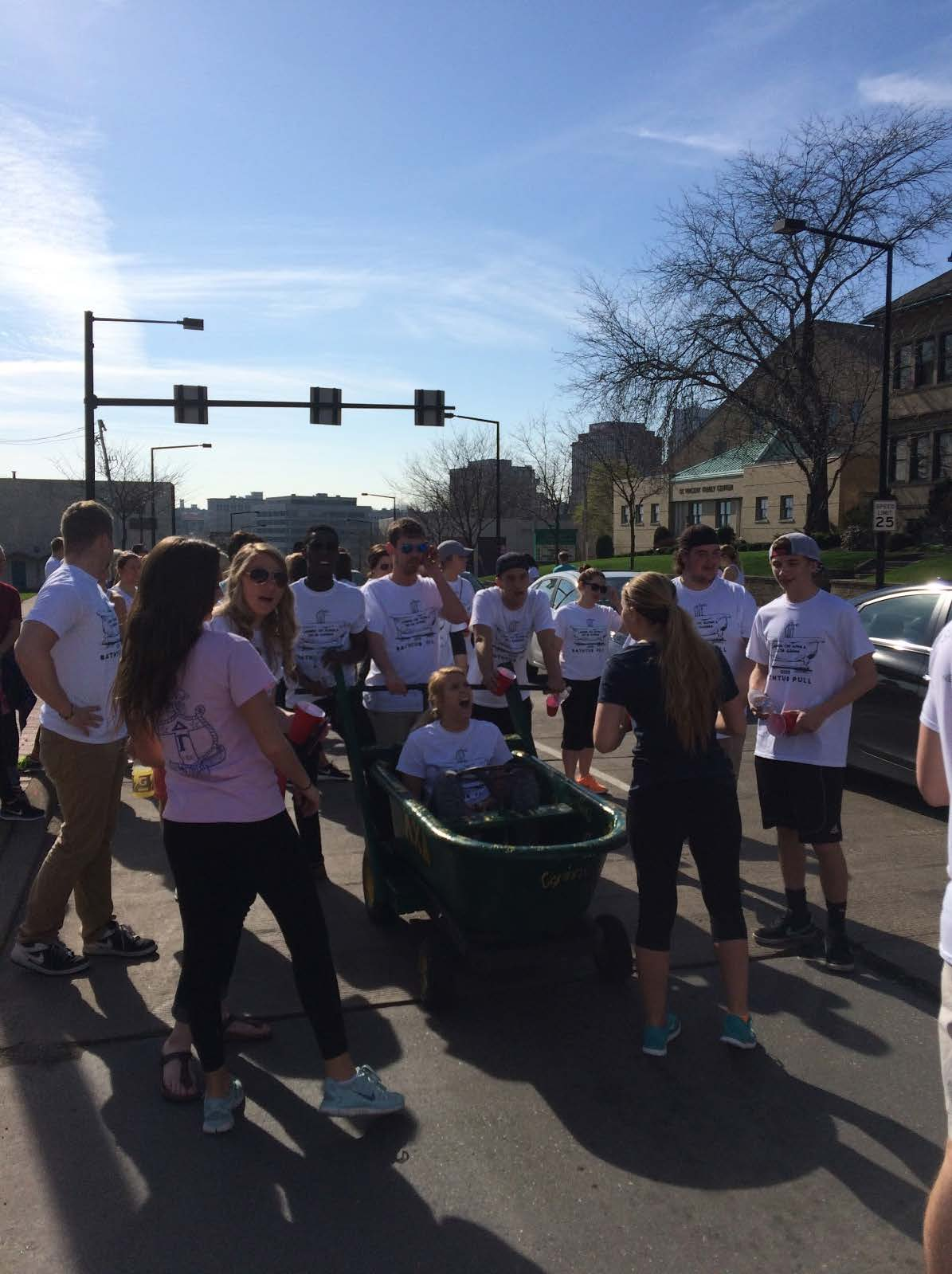 Lambda Chi Alpha brothers pull Delta Gamma sisters down Market Street during the five-mile annual bathtub pull.