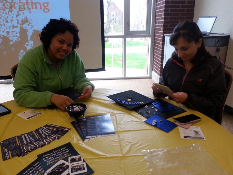 Seniors Destiny Huggins and Monica Langmeyer decorate their graduation caps.