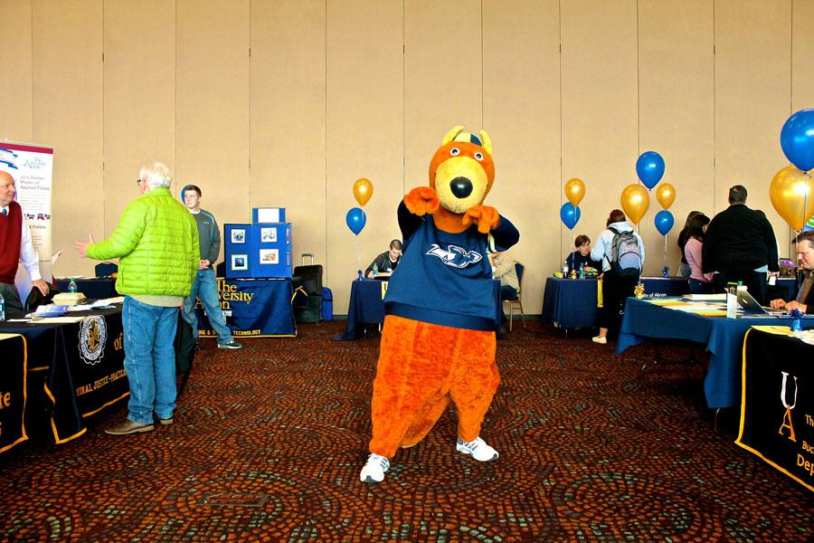 While students meander about and get information at the Majors Fair, Zippy encourages them to study what they love.