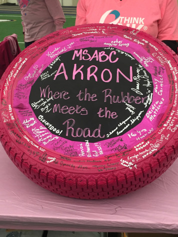 Survivors sign pink tire in honor of breast cancer awareness month.