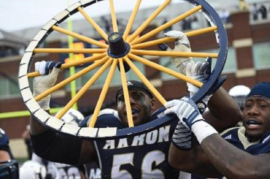 Isaiah Williams holds up the Wagon Wheel after the Zips win over Kent State