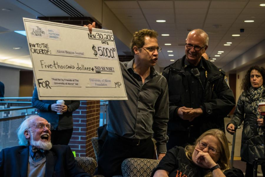 UA grad student Tom Guarino at Dec. 9's Board of Trustees protest, holding up a $5,000 check to parody the UA Foundation's payment of the Nov. 29 Akron Beacon Journal ad.