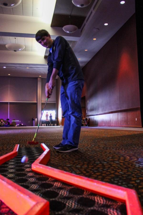 Logan Hershberger, the president of the Zips Programming Network, plays glow-in-the-dark mini golf during the Welcome Back Bash.