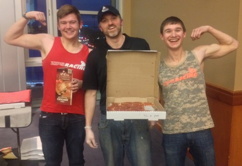 3 Guys Pizza employee showcases winning pizza besides students Ryan Harty (left) and Matthew Yoder (right)
