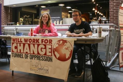 Paul Lewandowski and Jessie Repko promote their campus organization's event, Tunnel of Oppression.