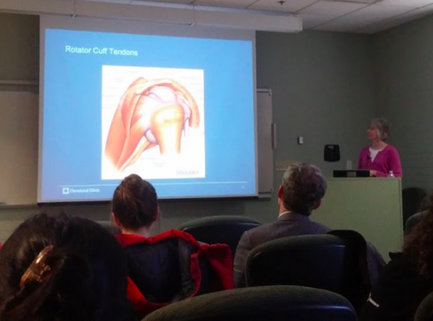 Kathleen Dervin gestures at an image of a rotator cuff.