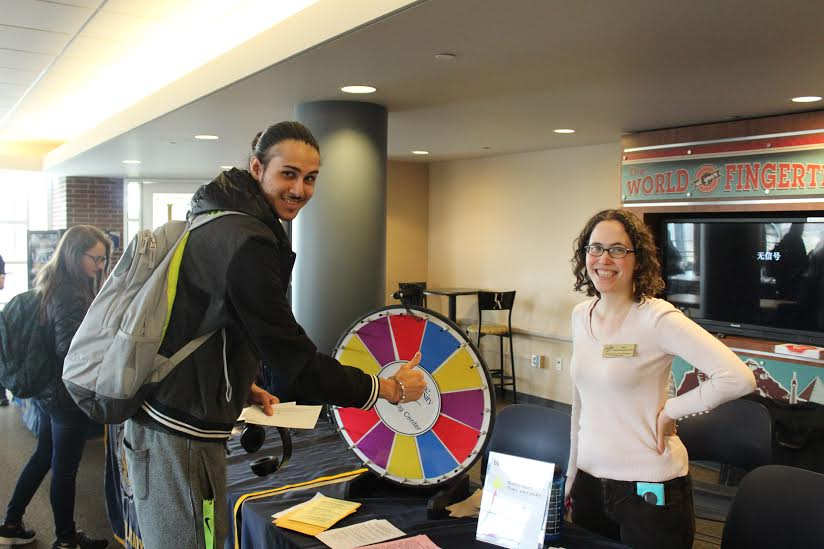 UA student Harwin Der, spinning the wheel to win a prize from the Counseling Center table.