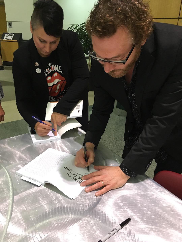 UA English professor David Giffels (right) signs a copy of