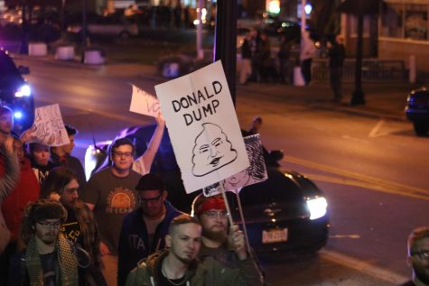 Demonstrators hold signs as they march down W. Market Street during the protest in Highland Square on Tuesday night.