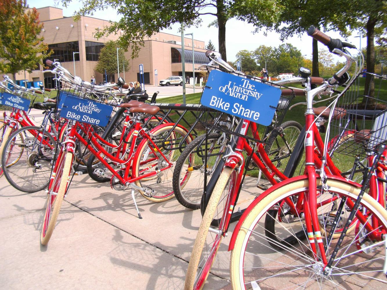The bright red bikes on their bike racks in front of the Student Recreation and Wellness Center.