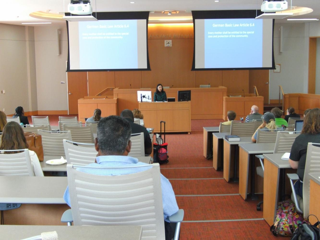 Suk lectures to a room full of students and staff in the Brennan Courtroom in the School of Law.