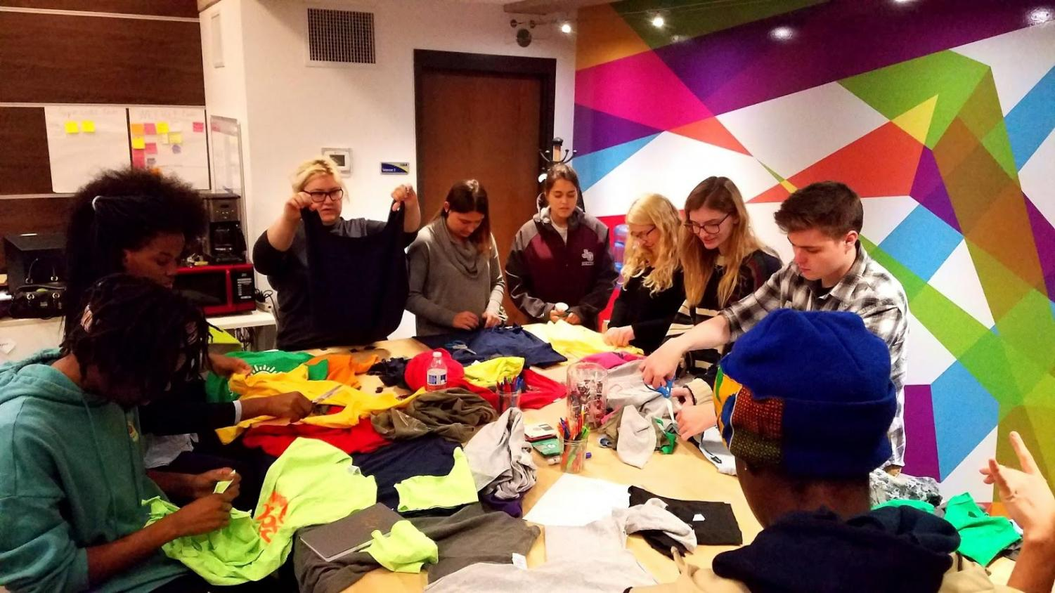 Students begin to make reusable grocery bags out of t-shirts.