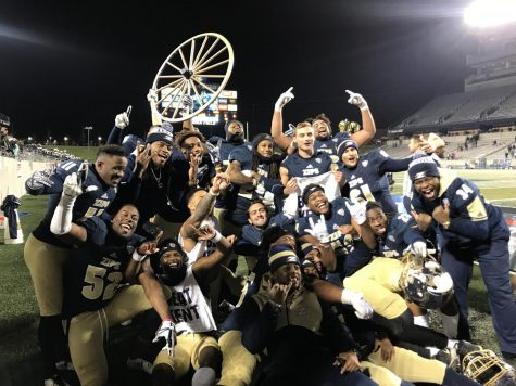 Members of the Akron Zips football team celebrate with the Wagon Wheel following their 24-14 win over Kent State at InfoCision Stadium on Tuesday.