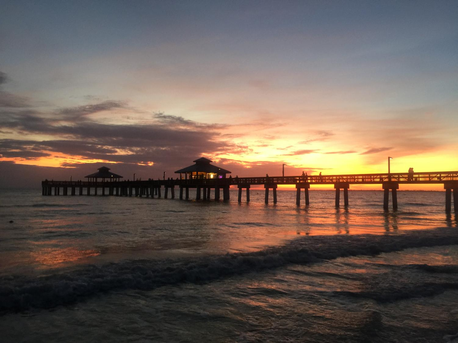 The Sun sets behind the Times Square Pier at Fort Myers Beach.