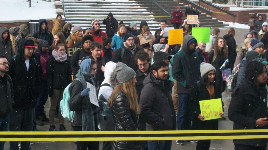 Students, faculty and staff stand outside of Bierce Library for the walkout at The University of Akron.