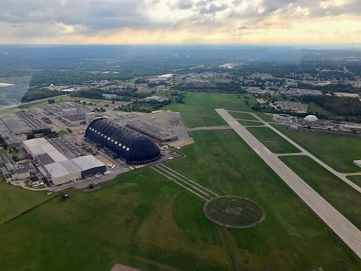 Wingfoot Three flies over the Akron Airdock at Akron Executive Airport. The massive facility was once home to the Goodyear-Zeppelin Corporation, where many airships were built for the U.S. Navy during the 1930s.