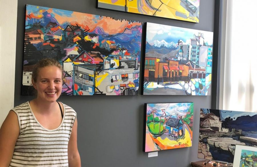 Lizzi Aronhalt stands in her studio in front of several original art pieces. Aronhalt is an Ohio licensed art teacher and offers art lessons individually, as well as in a small group setting.