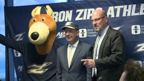 Zippy (left) and Larry Williams, Director of Athletics (right), welcome head coach Chris Sabo (center) to UA. (Image via WKYC)