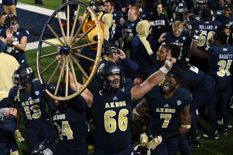 Zips football players and Zippy celebrating with the Wagon Wheel after fourth consecutive win against Kent State. (Photo courtesy of the Akron Zips)