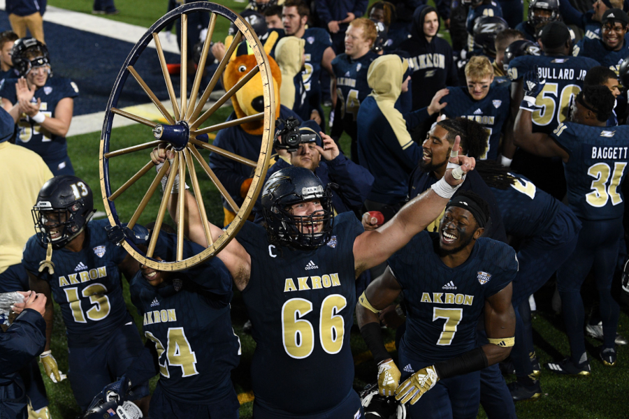 Zips+football+players+and+Zippy+celebrating+with+the+Wagon+Wheel+after+fourth+consecutive+win+against+Kent+State.+%28Photo+courtesy+of+the+Akron+Zips%29