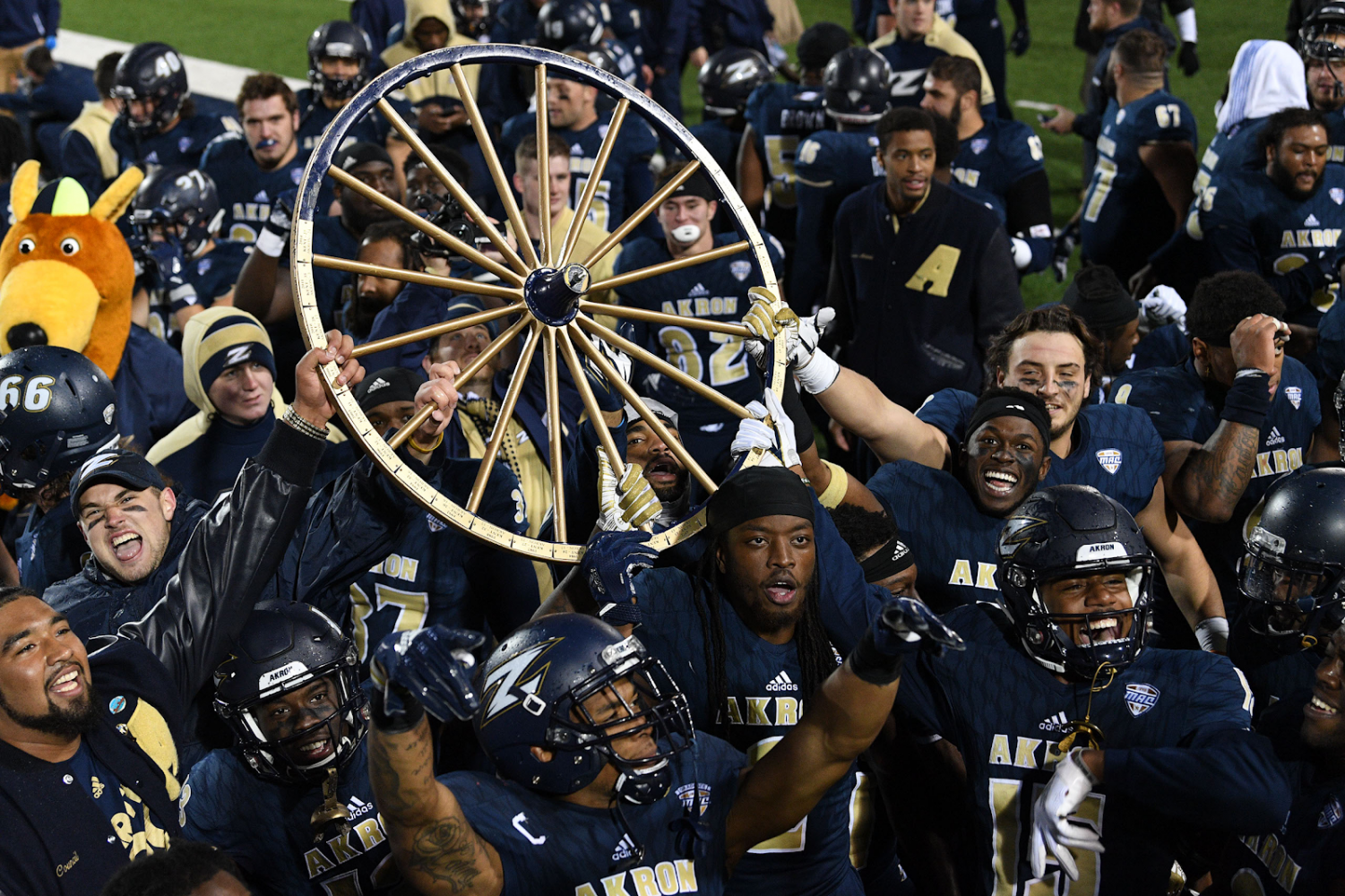 Zips football players celebrate with the Wagon Wheel after the Oct. 20 match against Kent State with a 24-23 win. (Photo courtesy of the Akron Zips)