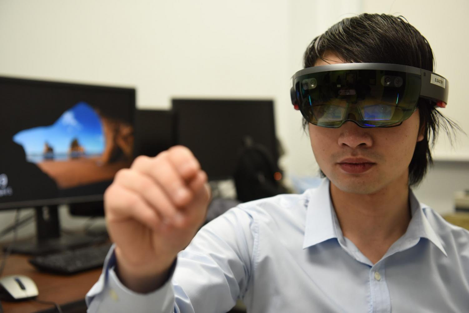 Bach Tran interacts with virtual images on the Microsoft HoloLens.