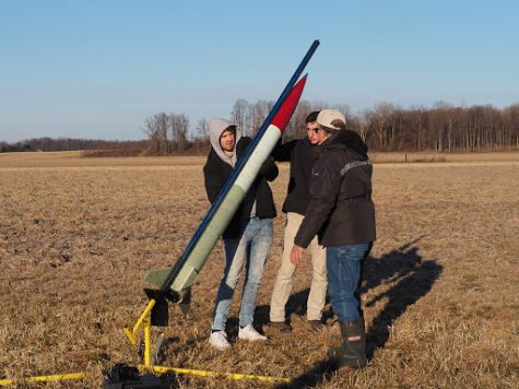 Akronauts Adam McElfresh (left) and Matthew Reppa, along with Chris Pearson, the team's mentor, load their rocket onto the launch rail, which keeps the rocket going straight as it initially builds up speed. This test launch was held at the National Association of Rocketry field located in Amherst.