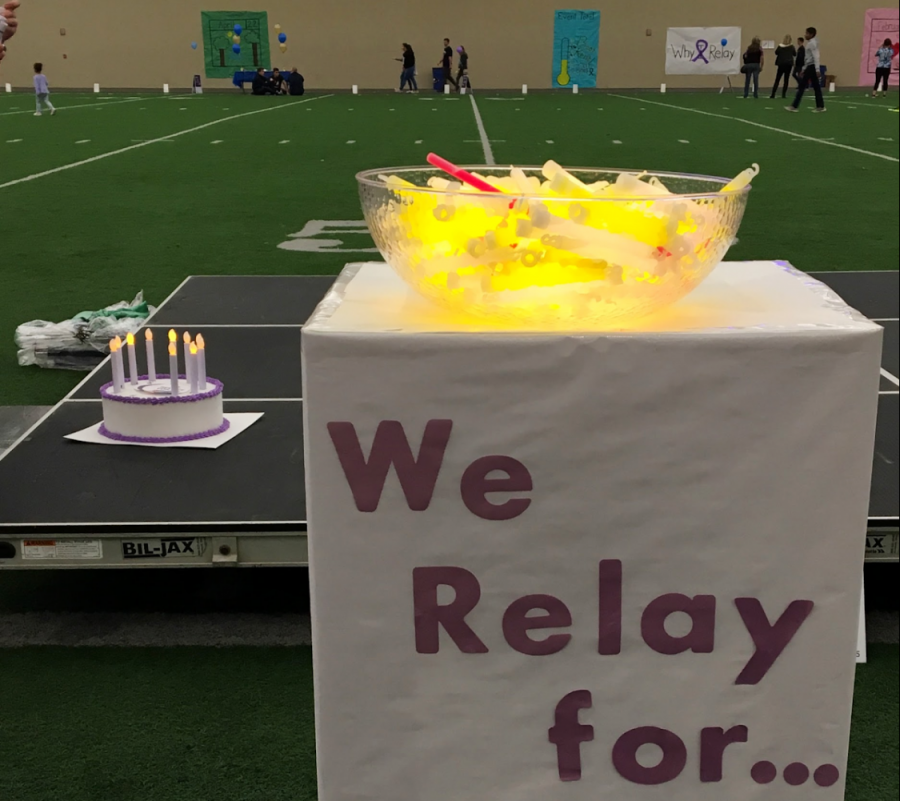 After finishing the Luminaria Ceremony lap at the 2018 Relay For Life, participants add glow sticks to the