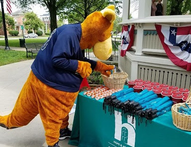 Zippy looks at a table with items from the Rape Crisis Center.