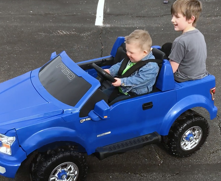 Nathan Ramey gives older brother, Trent, a ride in his newly adapted Power Wheels vehicle.