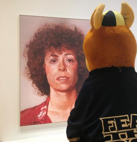 The University of Akron's mascot, Zippy, looking into the eyes of  Chuck Close's curly-haired Linda.