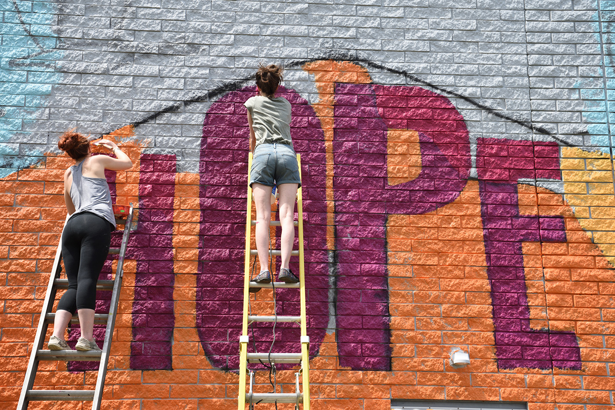The Art Bomb Brigade works on a painting of hope on the side of a building in the Akron area.