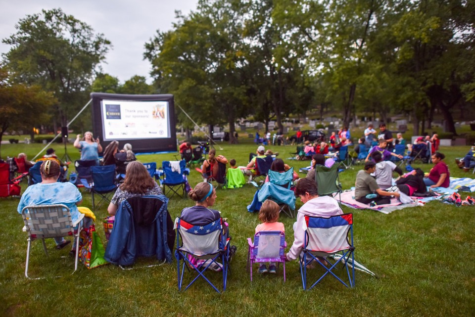 People gather around in the cemetery to watch movies on the projector screen.