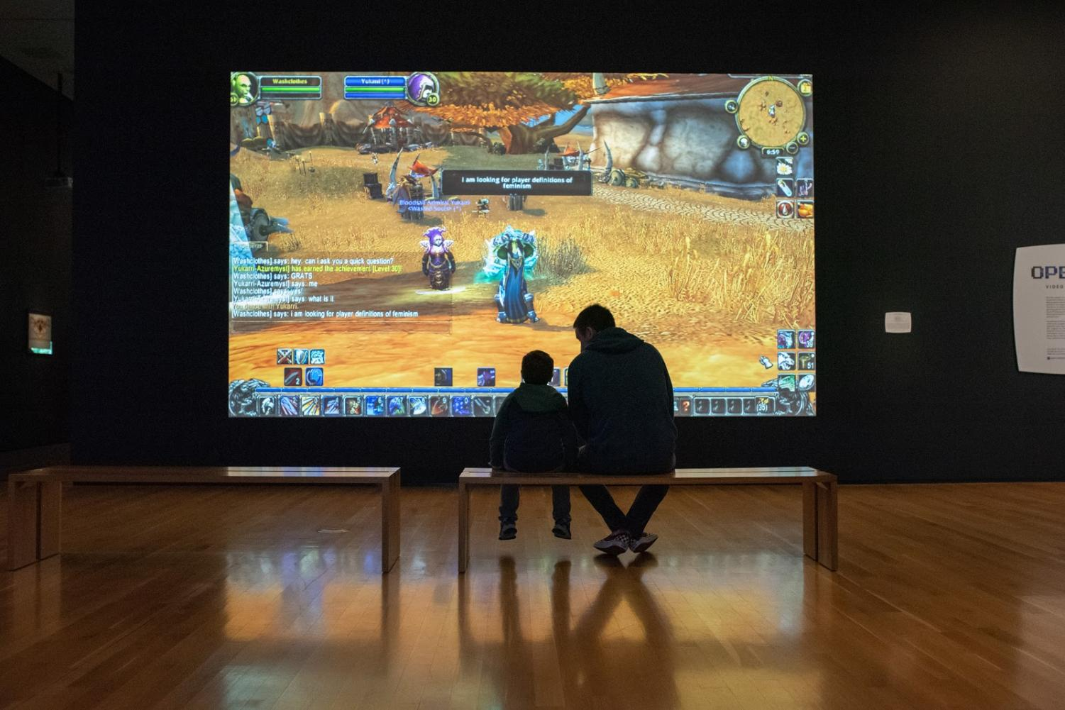 Two visitors observe Angela Washko's performances for video based on the popular role-playing game World of Warcraft.