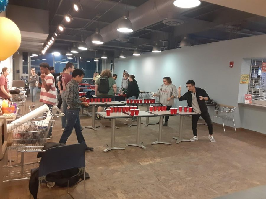 Students participating in the Root Beer Pong Championship during the kegger event.
