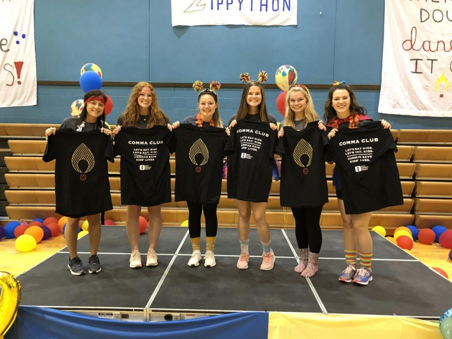 Members of Zippython pose with members of the Comma Club while holding shirts showing the importance of commas in sentences.