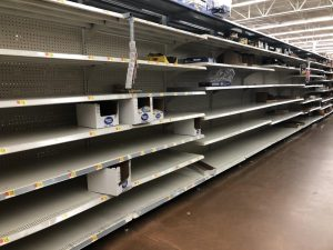 "Aisles that normally house non-perishable foods and other supplies are nearly empty after shoppers engage in ""panic buying"" due to COVID-19."